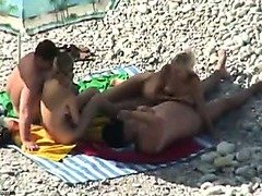 2 tanned couples have fun on a beach